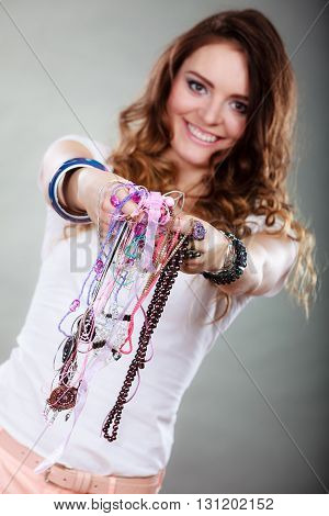 Happy pretty young woman wearing bracelets and rings holding many plentiful of precious jewelry necklaces beads. Portrait of gorgeous fashion girl in studio on gray.