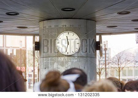 blurred people in front of a clock Alexanderplatz Berlin