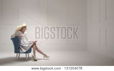 Elegant blonde in an empty room