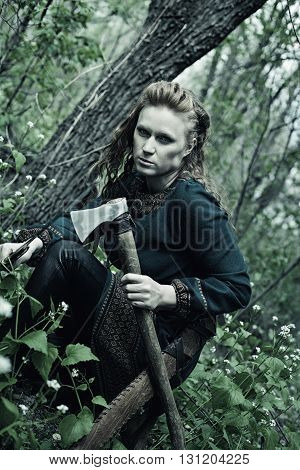 Serious redhead scandinavian woman posing with axe in a forest