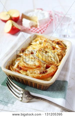 Gratin of potatoes apples and Camembert cheese on white table