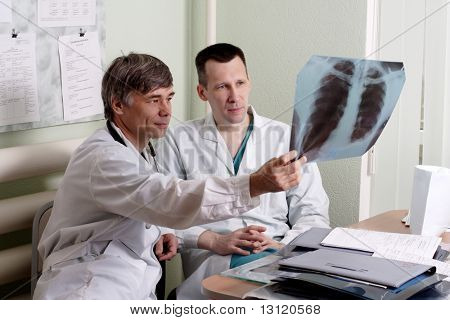 Two doctors review some case notes.
