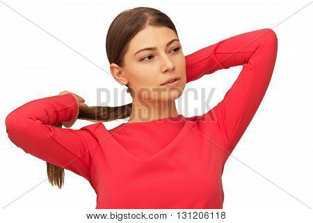 young woman holding hair tie and looking sideways isolated on white background
