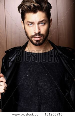 Handsome confident mature man with beard stands on wooden brown