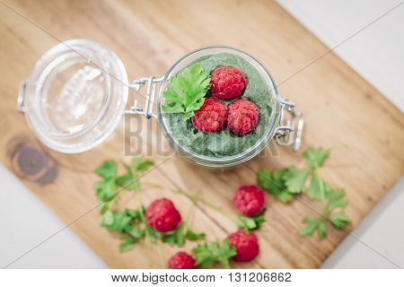 Green Super-useful Mousse With Raspberries. The View From The Top. Glass Jar Mousse On A Board Laid