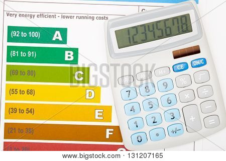 Calculator Over Colorful Energy Efficiency Chart