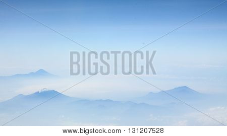 Blue sky with clouds and fog around the Mountains. It's on Java, Indonesia.