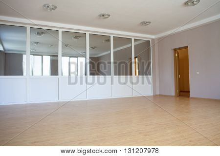 large room with a partition with mirrors