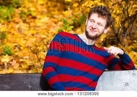 Season happiness and people concept. Young bearded man sitting relaxed on bench in autumnal park on sunny day