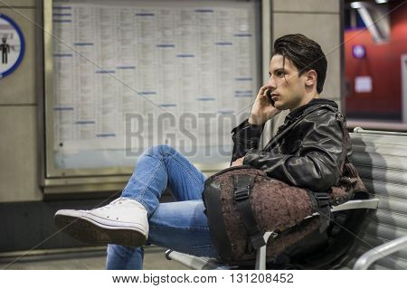 Young man traveling, sitting next to train timetable in railway station