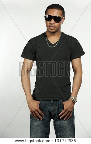 A young hip African American male wearing a black t-shirt with sunglasses in a studio setting on a white background.