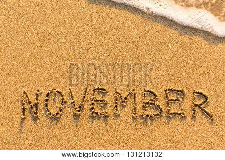 November - written by hand on a golden beach sand.