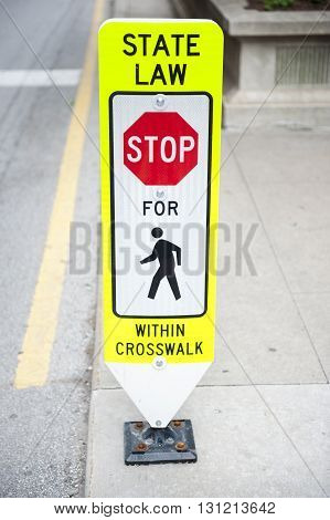 A traffic sign with state law on the street in front of the Chicago City Hall and County Building in Chicago, Illinois. It mentions the vehicles to watch over pedestrians walking.