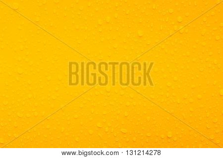 water drops on yellow metal texture and background.