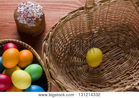 Easter cake and colored eggs in a wicker basket