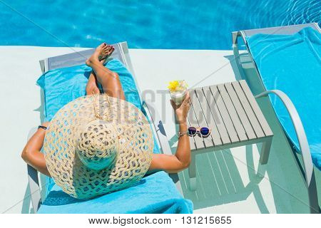 Pretty blond woman  enjoying a cocktail at the  swimming pool