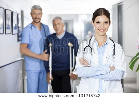 Female Doctor Standing With Colleague And Senior Patient In Back