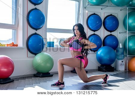 In gym. Image of nice brunette posing while exercising
