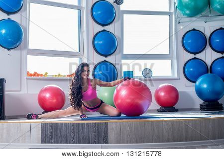At gym. Image of smiling brunette doing stretching exercise