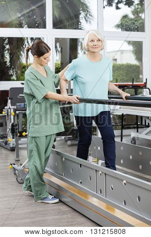 Physiotherapist Looking At Senior Patient Walking Between Bars