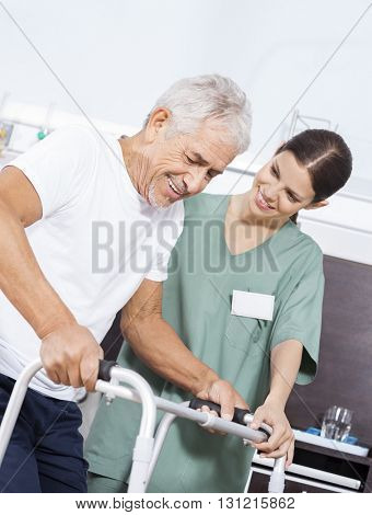 Nurse Looking At Senior Patient Using Walker In Rehab Center