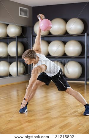 Man Exercising While Lifting Kettlebell On Hardwood Floor At Gym