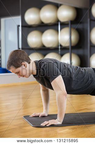 Man Performing Pushups On Mat In Gym