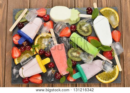 Ice cream popsicles ice and various fruits on a black plate