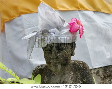 balinese statue wearing traditional headband and flower