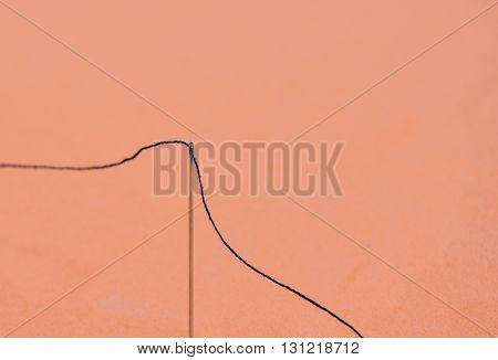 needle and black thread on red background