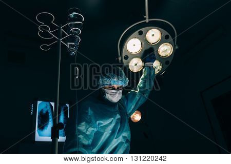 surgery, medicine and people concept - surgeon in mask adjusting lamp in operating room at hospital