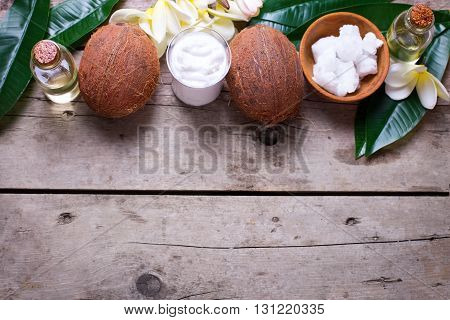 Coconuts coconut oil and milk on vintage wooden background. Selective focus. Natural organic spa products. Place for text.