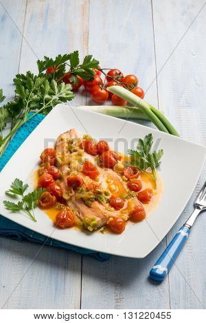 salmon trout fillet with leek and fresh tomatoes