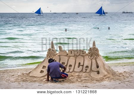 little boy making sand tower castle at white beach of  Boracay island  Philippines