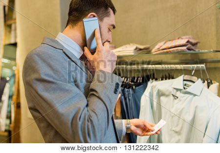sale, shopping, fashion, communication and people concept - close up of young man calling on smartphone and looking to shirt price tag at clothing store