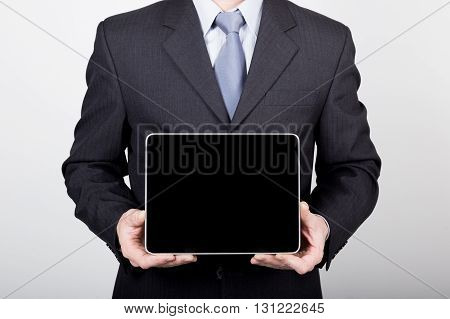 technology, internet and networking in business concept - businessman holding a tablet pc with blank dark screen. Internet technologies in business.
