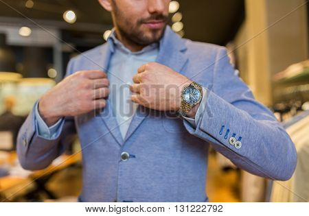 sale, shopping, fashion, style and people concept - close up of young man trying jacket at clothing store