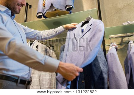 sale, shopping, fashion, style and people concept - close up of man choosing jacket at clothing store