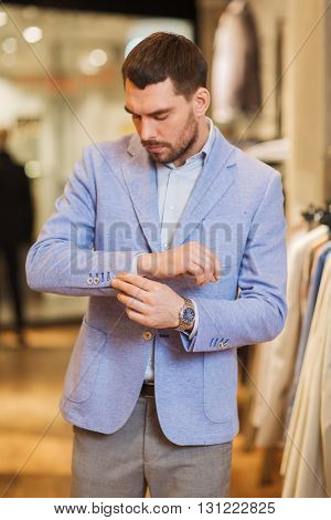 sale, shopping, fashion, style and people concept - elegant young man choosing and trying jacket on in mall or clothing store