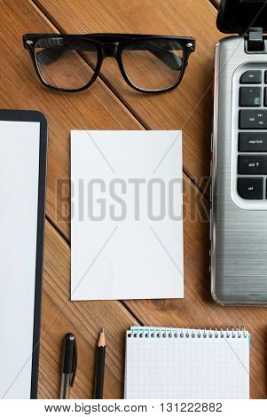 business and technology concept - close up of blank paper and office supplies on wooden table
