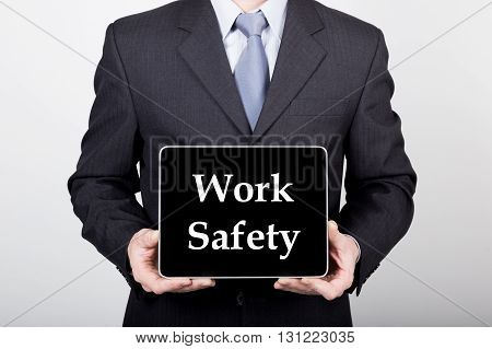technology, internet and networking in business concept - businessman holding a tablet pc with work safety sign. Internet technologies in business.