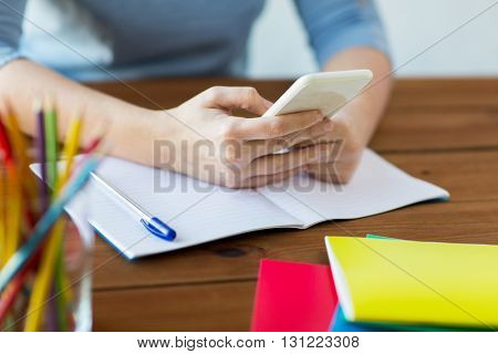 high school, education, people and learning concept - close up of young student or woman with smartphone and book writing to notebook at home