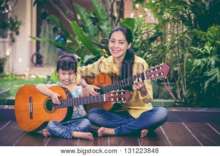 Happy family spending time together. Asian mother with daughter playing classic guitar at home. Pretty girl with thump up and looking at camera. Vintage picture style.