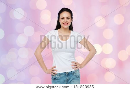 advertisement, clothing and people concept - happy smiling young woman or teenage girl in white t-shirt over rose quartz and serenity holidays lights background