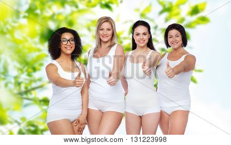 gesture, friendship, beauty, body positive and people concept - group of happy different women in white underwear showing thumbs up over green natural background