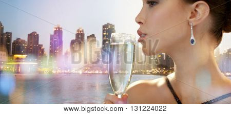 holidays, nightlife, drinks, people and luxury concept - close up of beautiful young asian woman drinking champagne at party over dubai city night lights background
