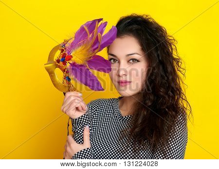 woman in carnival mask with feather, beautiful girl portrait on yellow color background, long curly hair