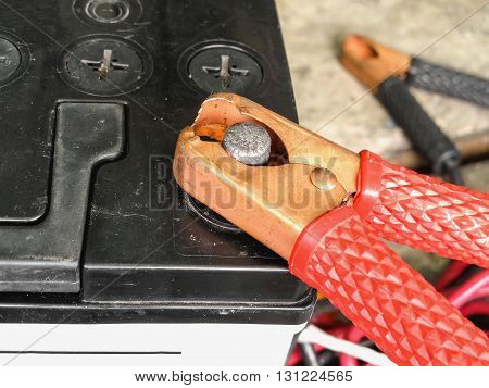 Red copper clamp with jumper cable for car battery charging selective focus