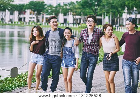 THree young Asian couple walking in the street together