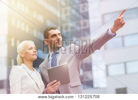 business, partnership, technology and people concept - serious businessman and businesswoman with tablet pc computer pointing finger to something over office building